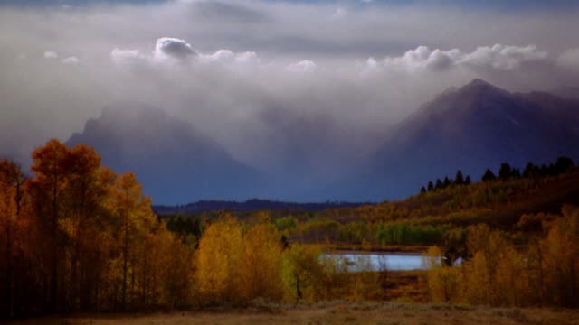 stockvideo's en b-roll-footage met wide shot pan valley with autumn trees and clouds over mountains in background / grand teton national park, wyoming - mount moran