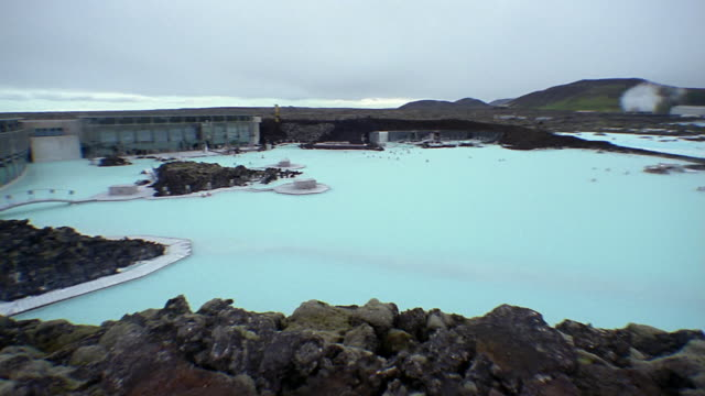 Wide shot pan view of the geothermal waters of the Blue Lagoon (Blaa Loninu) / Iceland