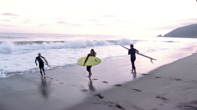 wide shot pan woman and two men carrying surfboards on beach / getting in water and paddling out in surf - 40 49 years stock videos & royalty-free footage