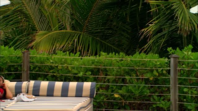 wide shot pan woman and young couple lying on poolside lounge chairs/ tilt up sea/ harbour island, bahamas - 男性と複数の女性点の映像素材/bロール