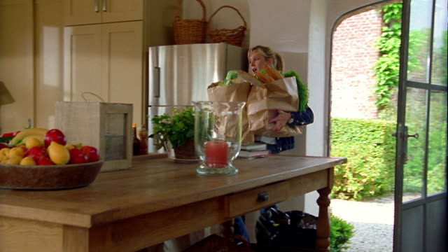 wide shot pan woman carrying grocery bags into kitchen, placing them on counter and answering telephone - grande gruppo di oggetti video stock e b–roll