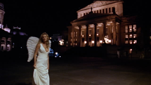 Wide shot pan woman dressed as angel walking in front of the Konzerthaus at night / Berlin, Germany