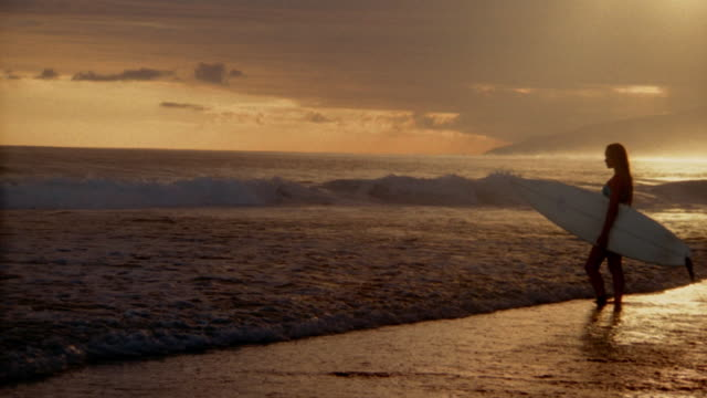 vidéos et rushes de wide shot pan woman holding surfboard in shallow water on beach at sunset / tahiti - cadrage aux genoux