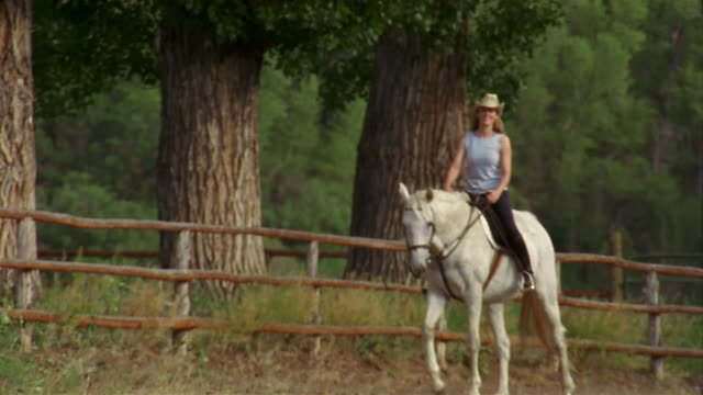 Wide shot pan woman riding white horse along fence with large trees in background / Carbondale, Colorado