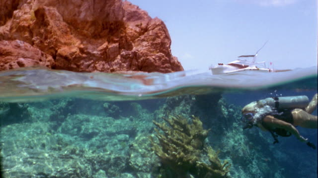 Wide shot pan woman scuba diving over coral reef with boat and rock formation above water