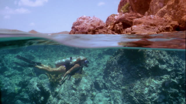 wide shot pan woman scuba diving over coral reef with boat and rock formation above water - oxygen tank stock videos and b-roll footage