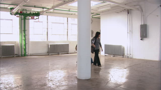 Wide shot pan woman showing man around empty loft space/ Brooklyn, New York
