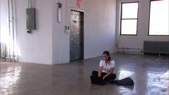 wide shot pan woman sitting on floor of empty loft space working on laptop/ brooklyn, new york - loft apartment stock videos & royalty-free footage