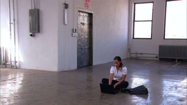 wide shot pan woman sitting on floor of empty loft space working on laptop/ brooklyn, new york - vindsvåning bildbanksvideor och videomaterial från bakom kulisserna