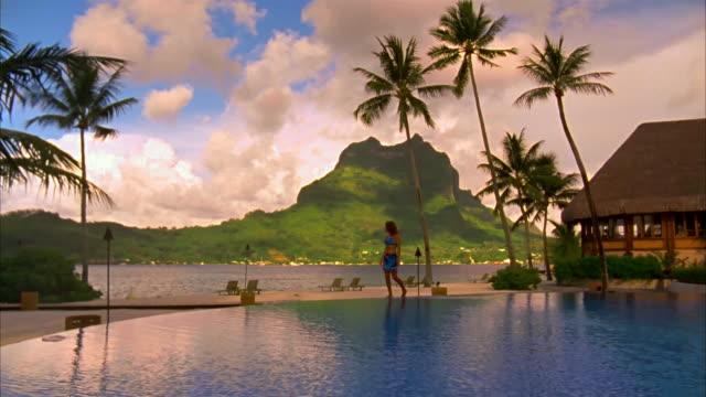 vídeos de stock, filmes e b-roll de wide shot pan woman walking along edge of infinity pool at resort with mount otemanu in background/ bora bora - lago infinito