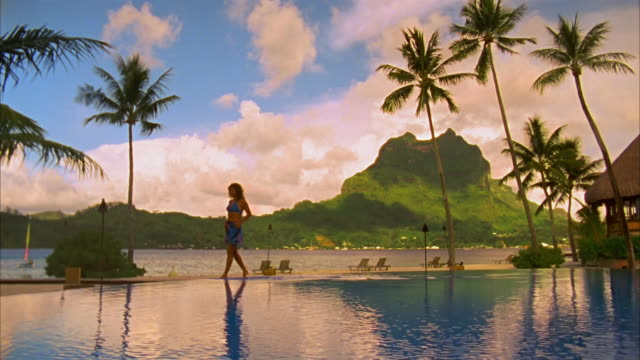 wide shot pan woman walking along edge of infinity pool at resort with mount otemanu in background/ woman diving into pool and swimming toward camera/ bora bora - stehendes gewässer stock-videos und b-roll-filmmaterial