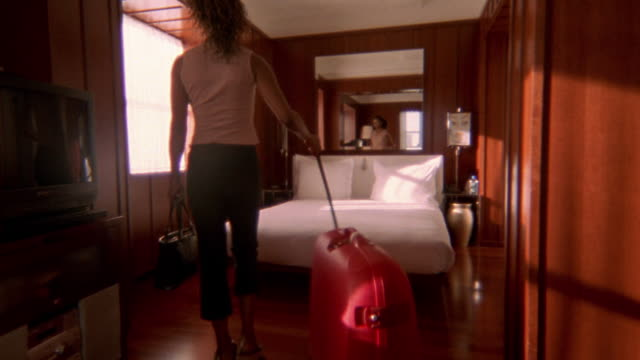 wide shot pan young black woman pulling large red suitcase into hotel room / stretching - double bed stock videos & royalty-free footage