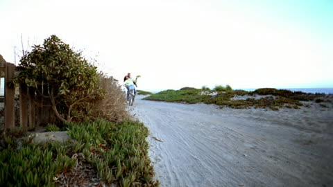 vidéos et rushes de wide shot pan young couple riding on bicycle by beach with woman on front holding flowers / california - océan pacifique nord