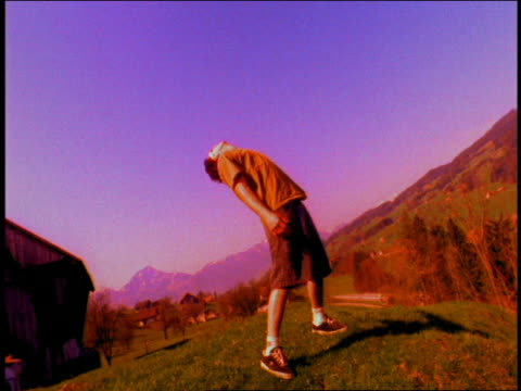 wide shot pan young man leaning back, looking up and raising arms on hillside / switzerland - menschlicher arm stock-videos und b-roll-filmmaterial