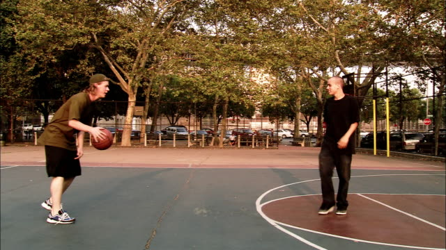Wide shot pan young men playing basketball at Martin F. Tenahey Playground / New York City