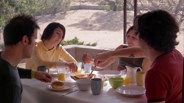 vídeos y material grabado en eventos de stock de wide shot pan young people serving waffles w/forks at outdoor breakfast table - waffles
