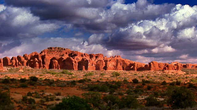 Wide shot pan zoom in time lapse storm clouds moving over rocky valley / mountains in background / Arches National Park, Utah