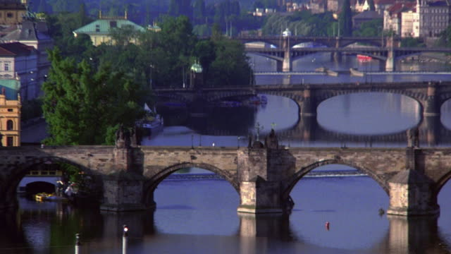 wide shot pan zoom out bridges on vltava river to city of prague / czech republic - charles bridge stock videos & royalty-free footage