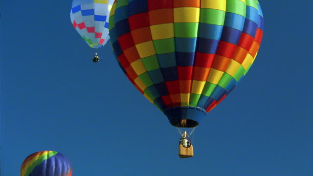 wide shot pan zoom out colorful hot air balloons in blue sky - medium group of objects stock videos & royalty-free footage