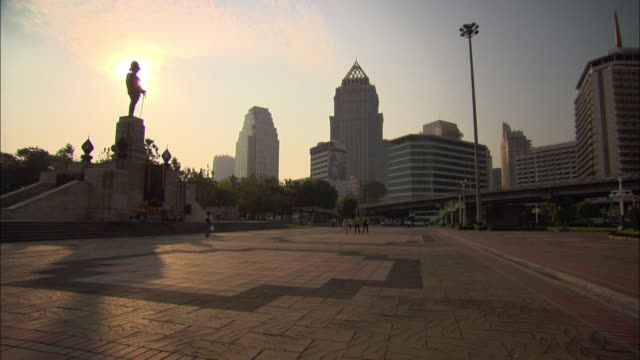 vidéos et rushes de wide shot pan-left - a statue of king rama vi towers over a plaza as traffic speeds past on a nearby street. / bangkok, thailand - gouvernement