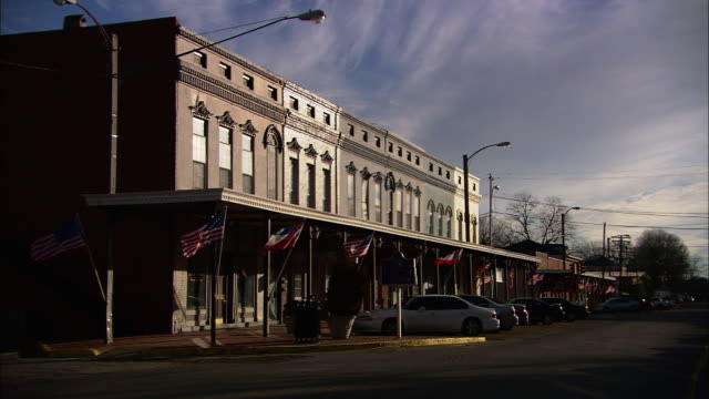 Wide Shot pan-left - American flags line storefronts in a small town where vehicles park. / Mississippi, USA