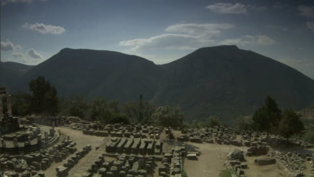 Wide Shot pan-left - Mountains tower in the background at the site of an ancient Greek temple. / Greece