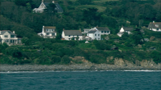 Wide Shot pan-left static - Homes overlook the ocean in Coverack, England. / Coverack, England