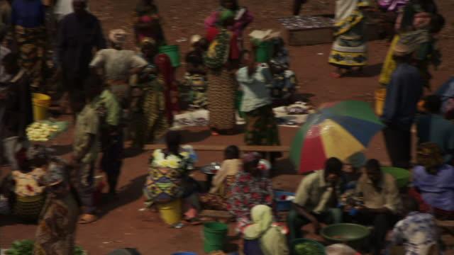 wide shot pan-left static - shoppers walk among rows of vendors at an outdoor market on the waterfront. / lake tanganyika, tanzania - タンザニア点の映像素材/bロール