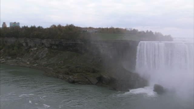vidéos et rushes de wide shot pan-left zoom-out - water cascades over niagara falls / ontario, canada - rivière niagara