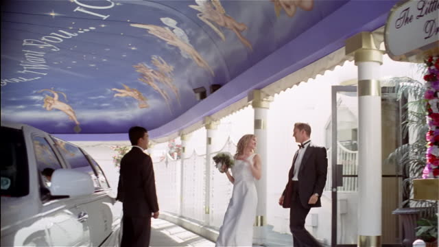 wide shot panning bride and groom leaving drive-thru wedding chapel / kissing and getting into limousine in carport - limousine luxuswagen stock-videos und b-roll-filmmaterial