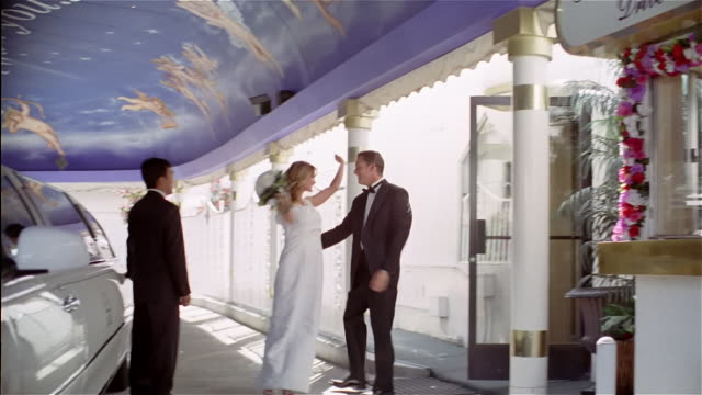 wide shot panning bride and groom leaving drive-thru wedding chapel / kissing and getting into limousine in carport - tuxedo stock videos and b-roll footage