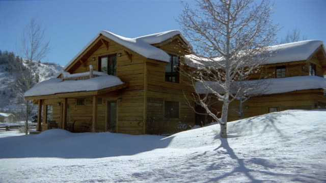 wide shot panning country house covered with snow / jackson hole, wyoming - capanna di legno video stock e b–roll