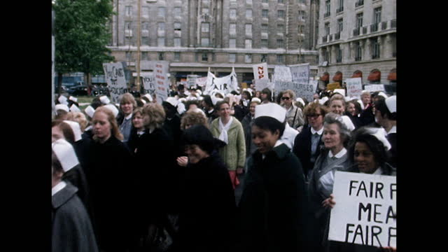 wide shot, panning left following nhs nurses marching for fair pay on the streets of london; 1974. - wide stock videos & royalty-free footage