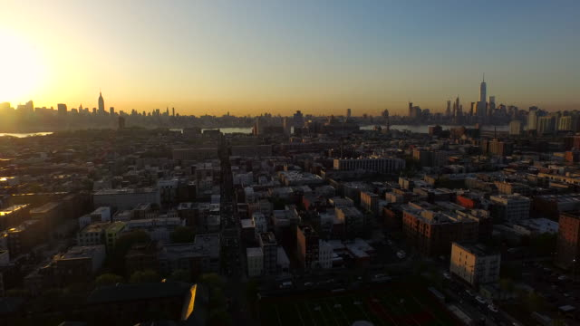 wide shot panning left over hoboken with nyc skyscrapers in distance at sunrise - ジャージーシティ点の映像素材/bロール