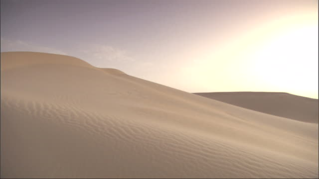 Wide Shot, pan-right - A bright yellow sun rises against a backdrop of golden sand dunes / Egypt