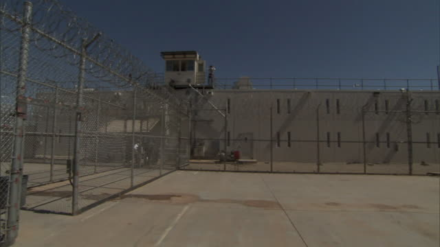 Wide Shot pan-right - A guard tower overlooks a concrete prison yard. / California, USA