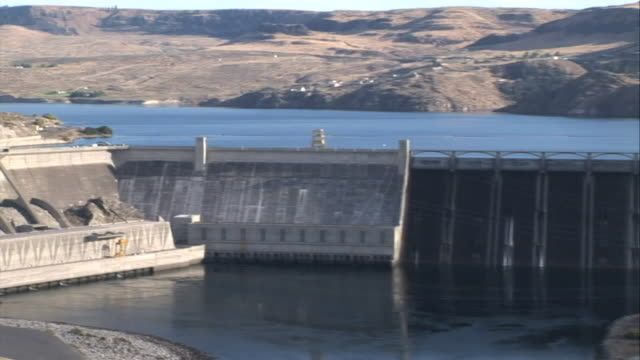 wide shot pan-right - a huge dam creates a reservoir / grand coulee dam, washington - bundesstaat washington stock-videos und b-roll-filmmaterial