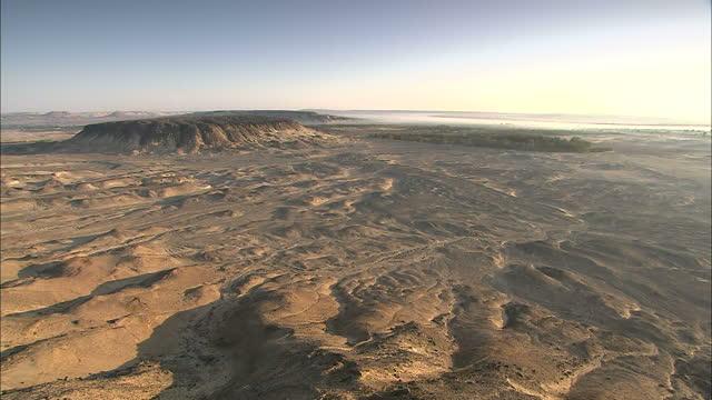 Wide Shot pan-right - Rugged hills stretch across a vast desert / Sahara, Egypt