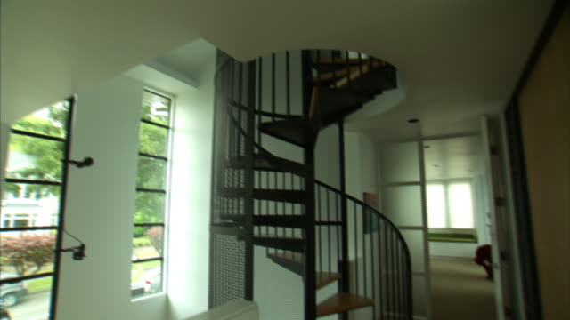 wide shot pan-right tilt-down - a spiral staircase leads to the second floor of a house next to a contemporary bedroom. / seattle, wa - spiral staircase stock videos & royalty-free footage