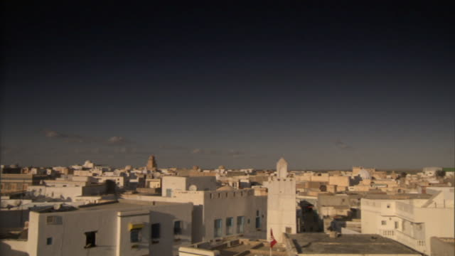 Wide Shot pan-right - White buildings contrast with a deep blue sky in Libya. / Libya