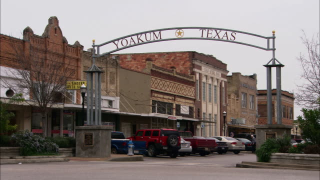 wide shot pan-right zoom-out - a sign stretches over an old-fashioned main street. / yoakum, texas, usa - centro commerciale suburbano video stock e b–roll