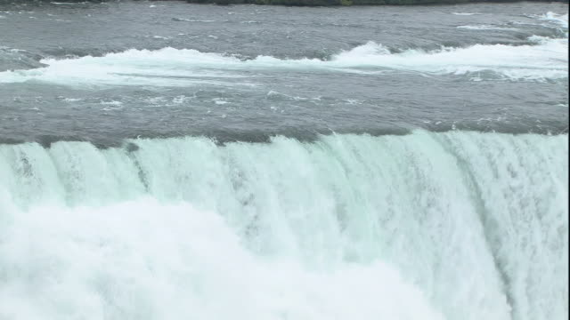stockvideo's en b-roll-footage met wide shot pan-right zoom-out - water rushes over niagara falls. / niagara falls, new york, usa - niagara falls city staat new york