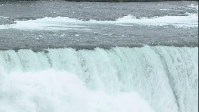 vídeos de stock e filmes b-roll de wide shot pan-right zoom-out - water rushes over niagara falls. / niagara falls, new york, usa - niagara falls city estado de nova iorque