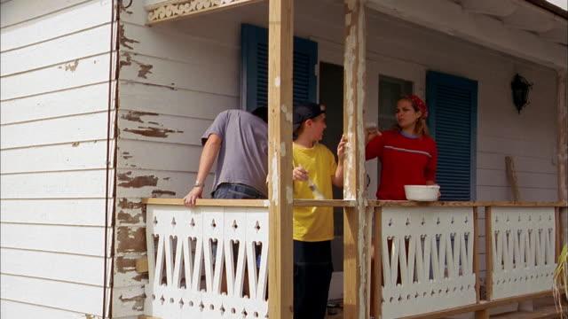 vídeos de stock, filmes e b-roll de wide shot parents and son painting porch of house - dois genitores