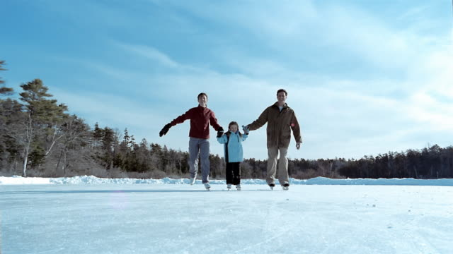 wide shot parents holding hands and skating with daughter on frozen pond toward cam / cape elizabeth, maine - eislaufen stock-videos und b-roll-filmmaterial