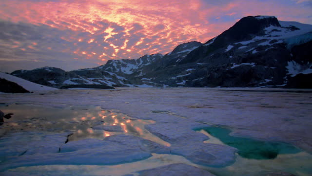 Wide shot partially frozen lake with mountains and snow in background at dusk / Whistler, British Columbia, Canada