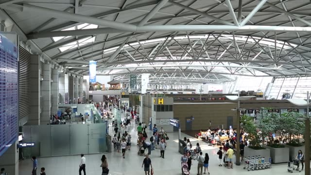 stockvideo's en b-roll-footage met wide shot passengers walk through terminal at incheon international airport in incheon south korea on thursday aug 8 high angle views passengers... - incheon