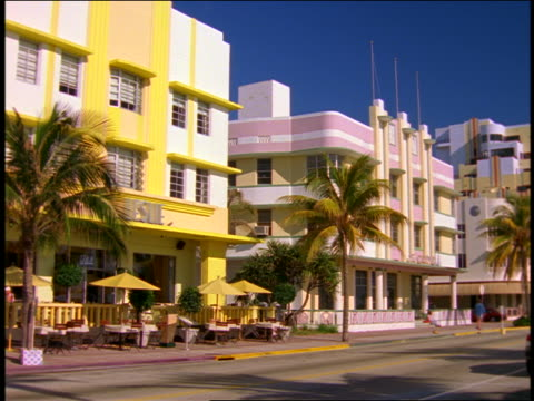 wide shot pastel colored cafe + palm trees along street / south beach / miami, florida - south beach stock videos & royalty-free footage