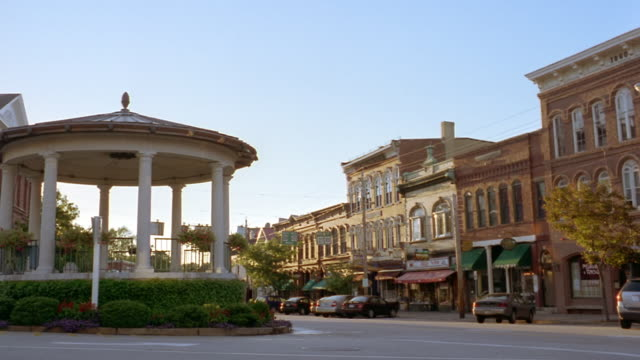 wide shot pavilion with columns and storefronts on main street of small new england town / camden, maine - small town stock videos & royalty-free footage