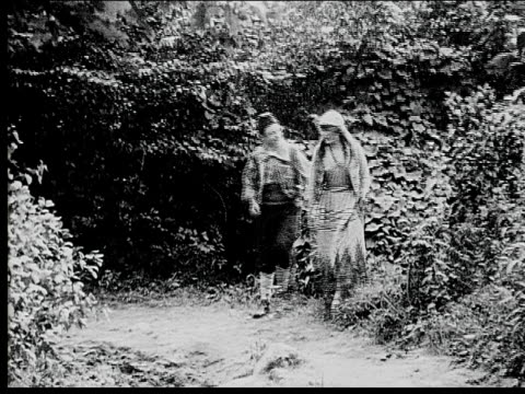 1916 b/w wide shot peasant couple walking in woods and kissing - 1916 stock videos & royalty-free footage